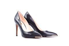 Chaussures noires de talon haut d'isolement sur le fond blanc Images stock