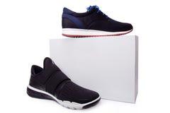 Chaussures noires du sport des hommes près du boîtier blanc Photographie stock