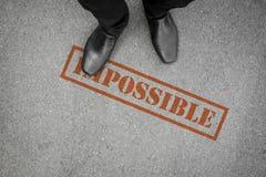Chaussures noires faisant un pas sur le mot impossible sur le plancher Photos libres de droits