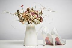 Chaussures nuptiales et fleurs sèches dans le vase images libres de droits