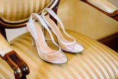 Chaussures nuptiales sur une chaise avec une tapisserie d'ameublement d'or et des poignées en bois image libre de droits