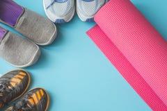 Chaussures oranges, bleues, et grises de sport avec le tapis rose de yoga Photos stock
