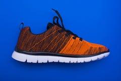 Chaussures oranges et noires de femme de sport d'isolement sur le fond bleu Images stock