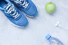 Chaussures plates de sport de configuration, bouteille de l'eau et écouteurs Photographie stock libre de droits