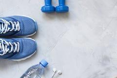 Chaussures plates de sport de configuration, bouteille de l'eau, haltères et écouteurs o Photographie stock libre de droits