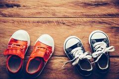 Chaussures pour des enfants sur le plancher en bois - mode de vie Photos stock
