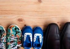 Chaussures pour la famille entière sur le plancher en bois Image stock