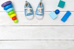 Chaussures pour le petit garçon et les cubes en bois sur un fond en bois Photos stock