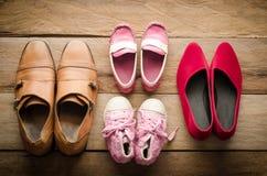 Chaussures, quatre paires de papa, maman, fille et fils - le concept de la famille photographie stock libre de droits