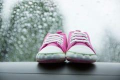 Chaussures roses d'enfant en bas âge d'espadrilles sur le tableau de bord de la voiture Photographie stock libre de droits