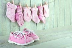 Chaussures roses d'enfant en bas âge sur le fond vert clair en bois Photographie stock