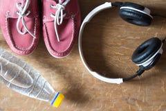 Chaussures roses de sport, écouteurs, bouteille de l'eau Paires d'espadrilles Photos stock