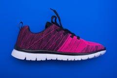 Chaussures roses et noires de femme de sport d'isolement sur le fond bleu Photographie stock libre de droits