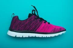 Chaussures roses et noires de femme de sport sur le fond de turquoise Photographie stock libre de droits