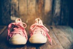 Chaussures roses pour des enfants sur le plancher en bois Images libres de droits