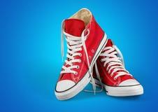 Chaussures rouges à la mode sur le fond bleu Images libres de droits