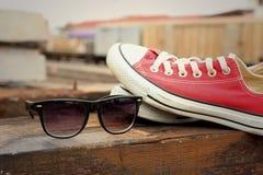 Chaussures rouges avec des lunettes de soleil sur le fond en bois brun Photographie stock