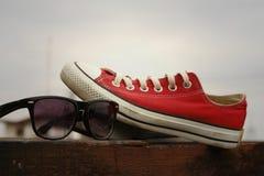 Chaussures rouges avec des lunettes de soleil sur le fond en bois brun Image stock