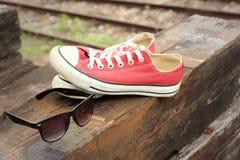 Chaussures rouges avec des lunettes de soleil sur le fond en bois brun Images stock