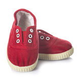 Chaussures rouges d'espadrilles pour des enfants d'isolement sur le fond blanc Photo libre de droits