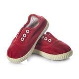 Chaussures rouges d'espadrilles pour des enfants d'isolement sur le fond blanc Photographie stock