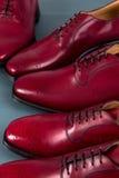 Chaussures rouges d'Oxford sur le fond bleu Trois brogues de paires Fin vers le haut Images libres de droits