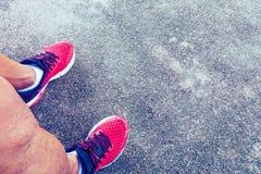 Chaussures rouges fonctionnant avec de l'eau potable sur le plancher en béton Photographie stock