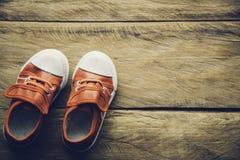 Chaussures rouges pour des enfants sur le plancher en bois Image libre de droits