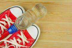Chaussures rouges sportives sur un fond en bois avec une bouteille de l'eau Photo libre de droits