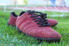 Chaussures rouges sur l'herbe verte avec le football de but Photo stock