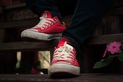 Chaussures rouges sur un plancher en bois - espadrilles Images stock