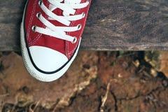 Chaussures rouges sur un plancher en bois - espadrilles Images libres de droits