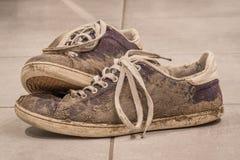 Chaussures sales avec la boue et le sol Images stock