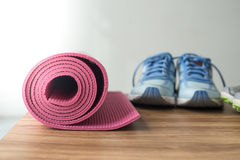 Chaussures sales de sport sur le plancher avec le tapis de yoga à la maison Photographie stock libre de droits
