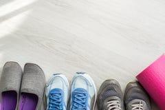 Chaussures sales de sport sur le plancher avec le tapis de yoga à la maison lifestyle Image stock