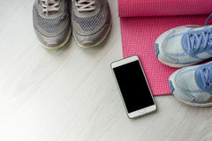 Chaussures sales de sport sur le plancher avec le tapis de yoga à la maison lifestyle Images stock