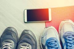 Chaussures sales de sport sur le plancher avec le tapis de yoga Photographie stock libre de droits