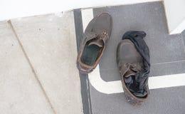 Chaussures sales et chaussettes noires sur le plancher dans le bureau Image stock