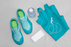 Chaussures sportives bleu-clair plates, une bouteille de l'eau, un T-shirt et écouteurs sur un fond concret gris Le concept d'une Photo stock