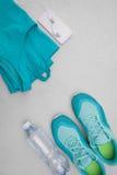 Chaussures sportives bleu-clair plates, une bouteille de l'eau, un T-shirt et écouteurs sur un fond concret gris Le concept d'une Photo libre de droits