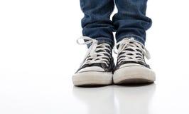 Chaussures sportives de cru sur le blanc avec des jeans Image libre de droits