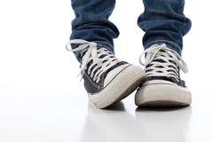 Chaussures sportives de cru sur le blanc avec des jeans Photographie stock libre de droits