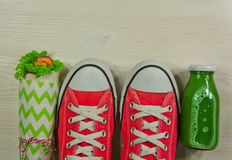Chaussures sportives rouges sur un fond en bois, avec du jus et un sandwich Image stock