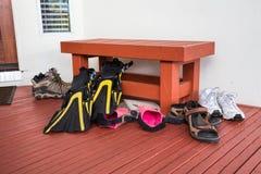 Chaussures sportives, sandales, ailerons de bain à la maison de vacances Photo stock