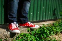 chaussures sur le béton parmi des buissons Photographie stock libre de droits