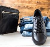 Chaussures sur une pile des jeans et sac sur un fond en bois photographie stock