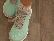 Chaussures vert clair de sport sur le plancher en bois Photos stock