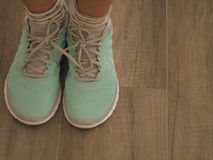 Chaussures vert clair de sport sur le plancher en bois Photo stock