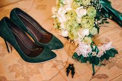 Chaussures vertes avec une jarretière verte pour la jeune mariée Photographie stock