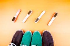 Chaussures vertes et brunes d'espadrille de suède avec des brosses sur le fond de papier jaune Images stock
